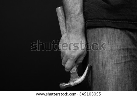 Black and white image of a close up of a man's hand holding a hammer