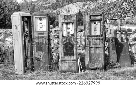 Black and White image of a collection of old rusting gas pumps found in an antique store in New Mexico