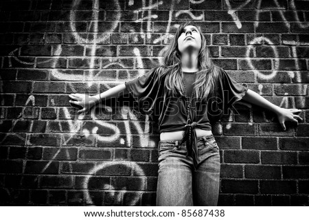 Black and White image of a fashionable teenage girl striking a dramatic pose, with arms spread, against a graffiti painted, urban wall - stock photo