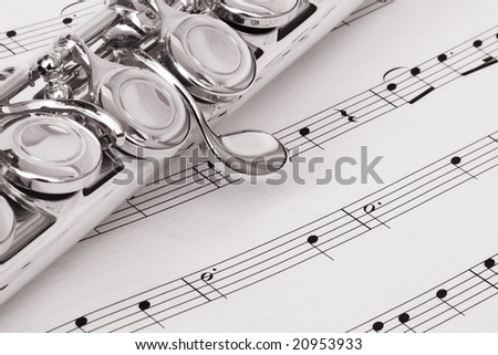 Black and White image of a flute on a background of music notes. Image is of some of the keys on the instrument. Flute is placed at a diagonal on the image. - stock photo
