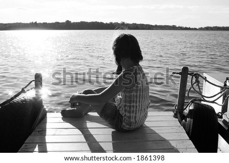 black and white image of a girl sitting on a pier, overlooking a lake - stock photo