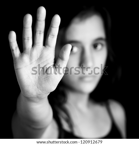 Black and white image of a girl with her hand extended signaling to stop useful to campaign against violence, gender or sexual discrimination (image focused on her hands) - stock photo