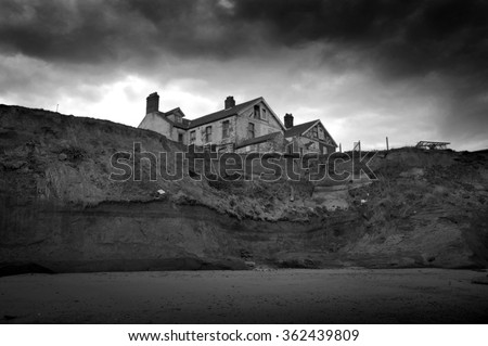 Black and white image of a house on the cliff edge at Happisburgh on the North Norfolk, uk, coast where erosion has made the homes unsafe. - stock photo