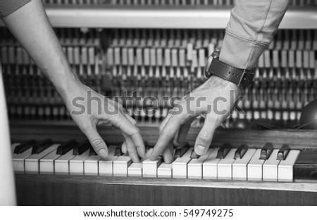 black and white image of a man and a woman playing the piano together. close-up