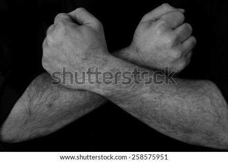 Black and white image of a mans arms crossed over each other - stock photo