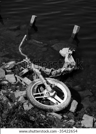 Black and white image of a motorcycle dumped in a pond - stock photo