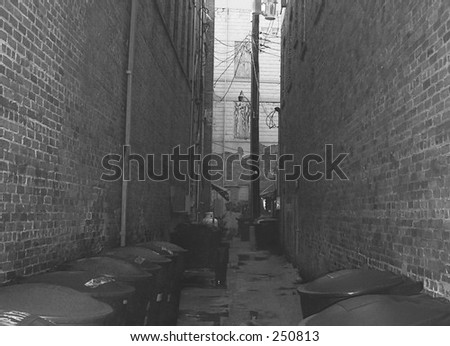Black and white image of a narrow urban alleyway with garbage cans lined against both sides. Older brick building are on either side. At the end of the alley is a power pole and another building - stock photo