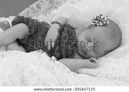 Black and white image of a newborn baby girl. - stock photo
