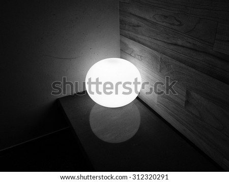 Black and white image of a round lamp in the corner on marble bench againt wooden and cement wall. Reflection of round lamp on marble bench. - stock photo