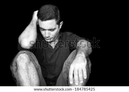 Black and white image of a sad and stressed young man sitting on the floor isolated on a black background