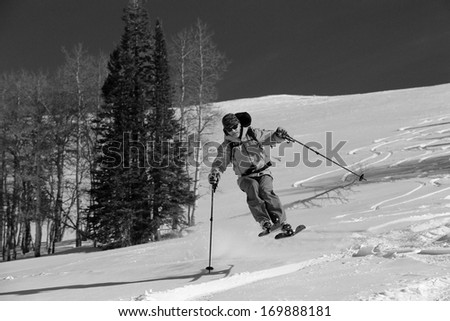 Black and white image of a skier jump turning in a meadow, Utah, USA. - stock photo