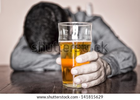 Black and white image of a sleeping drunk man (only his beer is in color) - stock photo