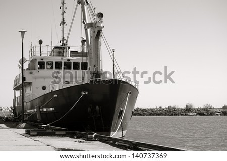 Black and white image of a small research vessel anchored at the pier. - stock photo