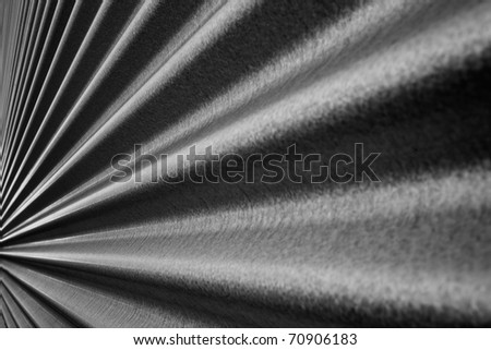 Black and white image of a steel metallic corrugated wall converging to a point - stock photo