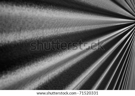 Black and white image of a steel metallic corrugated wall converging to a point on the right