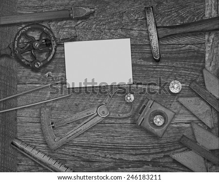 black and white image of a vintage jeweler tools and diamonds over wooden bench, space for text on a blank businesscard - stock photo