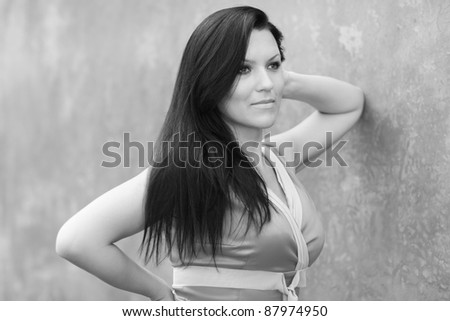 Black and white image of a woman leaning on the wall