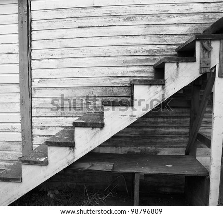 Black and white image of a worn and weathered staircase - stock photo