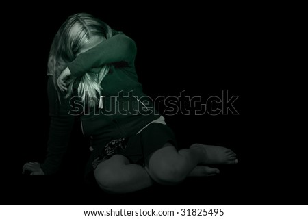 Black and white image of a young girl cowering in a dark room, hiding from the abuse - stock photo