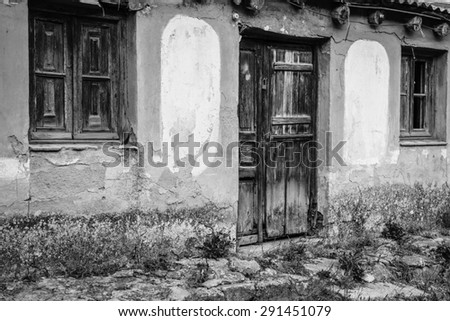 Black and white image of abandoned rustic aged home. Image include two old-fashioned window and one old door