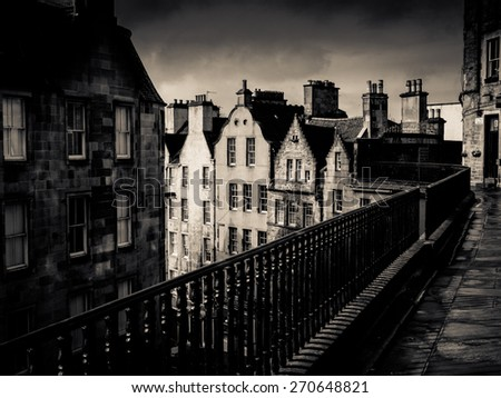 Black And White Image Of An Ancient Edinburgh Street Under A Stormy Sky - stock photo