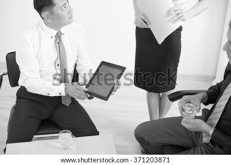 Black and white image of asian boss using tablet pc with his successful business team at background - stock photo
