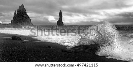 Black and white image of beach in Iceland with rocks off the shore and waves coming in.