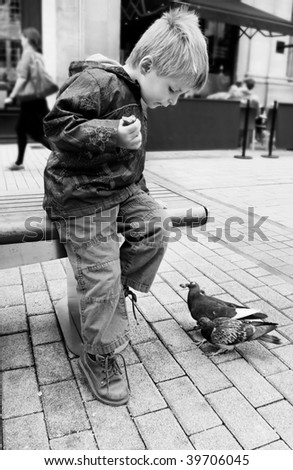 Black and white image of child eating outdoors surrounded by pigeons. - stock photo