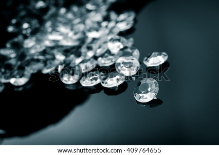 Black and white image of diamonds scattered on a shiny surface - stock photo