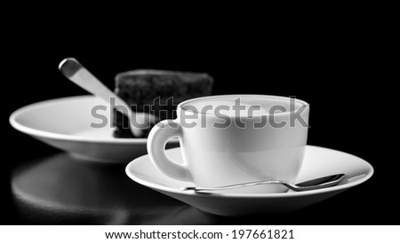 Black and white image of elegantly served chocolate cake and cappuccino. - stock photo