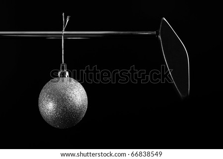 Black and white image of golf putter with Christmas ornament hanging - stock photo