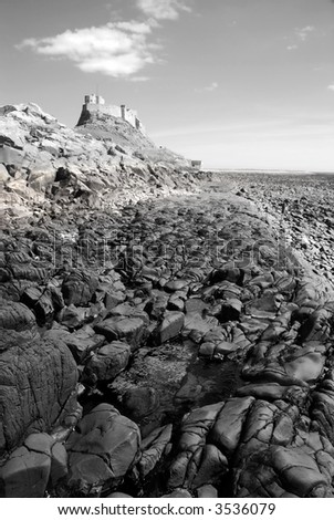 Black and white image of Lindisfarne Castle from beach