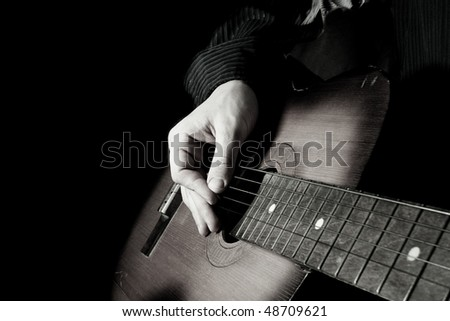 black and white image of man playing guitar - stock photo