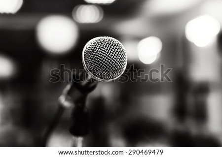Black and white image of microphone with lights in background - stock photo