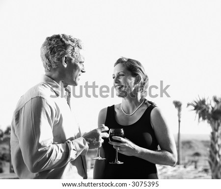 Black and white image of mid-adult Caucasian couple holding wine glasses and smiling at each other. - stock photo