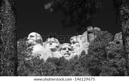 Black and white image of Mount Rushmore through the trees