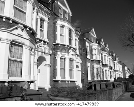 Black and white image of old fashioned typical Victorian terraced town houses architecture in London, England, UK. These residential homes are often turned into apartment flats - stock photo