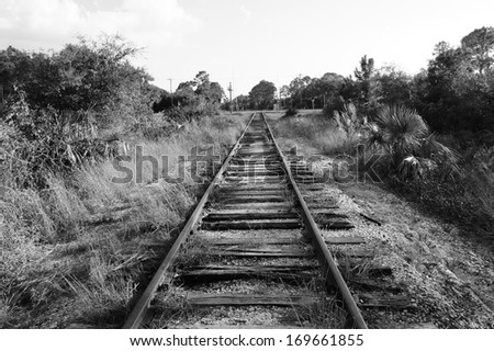 Black and white image of old railroad train track that converges into the distance at a street. - stock photo
