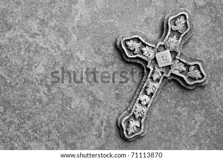 Black and white image of ornate stone cross on marble background with copy space. - stock photo