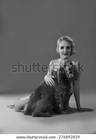 Black and white image of pretty girl petting a cute Spaniel dog - stock photo
