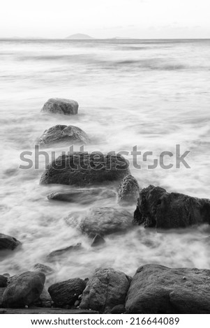 Black and white image of rocks at the beach in the Sunshine Coast, Queensland - Australia.