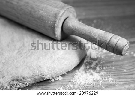 Black and white image of rolling pin and dough - stock photo