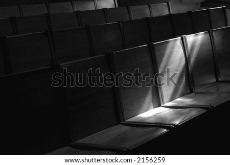 Black and white image of Rows of church pews with stream of light illuminating a seat - stock photo