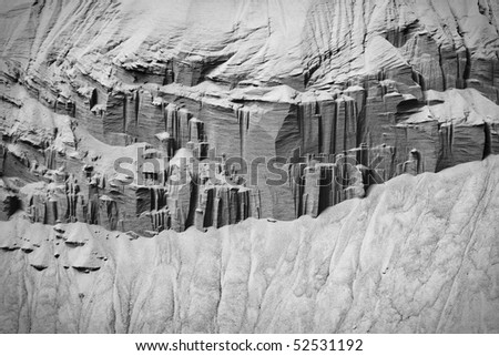 Black-and-white image of sand columns with banks of sand seeming to flow from the bottom. Horizontal shot.