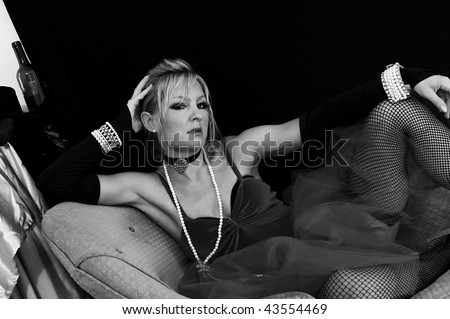 black and white image of sexy blond in fishnet stockings and old fashioned outfit looking directly at viewer. - stock photo