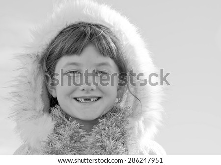 black and white image of six year-old red haired girl with two front teeth missing and wearing scarf and Eskimo style fur lined hood - stock photo
