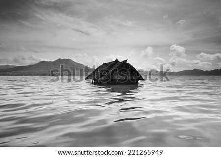 Black and white image of stationary water waves and Sunk house in lake batur  (image has certain noise when view full resolution) - stock photo
