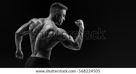 Black and white image of strong back athletic muscular man flexing his arms against black background Rear view of  handsome young shirtless fitness model with masculine physique