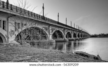 Black and white image of the MacArthur Bridge (once known as the Belle Isle Bridge) at sunset over the Detroit River in Detroit, Michigan. - stock photo