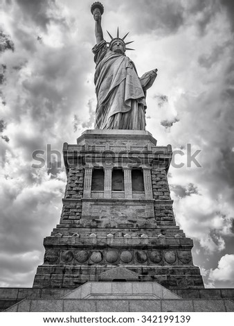 Black and white image of the Statue of Liberty in New York City with a dramatic cloudy sky - stock photo